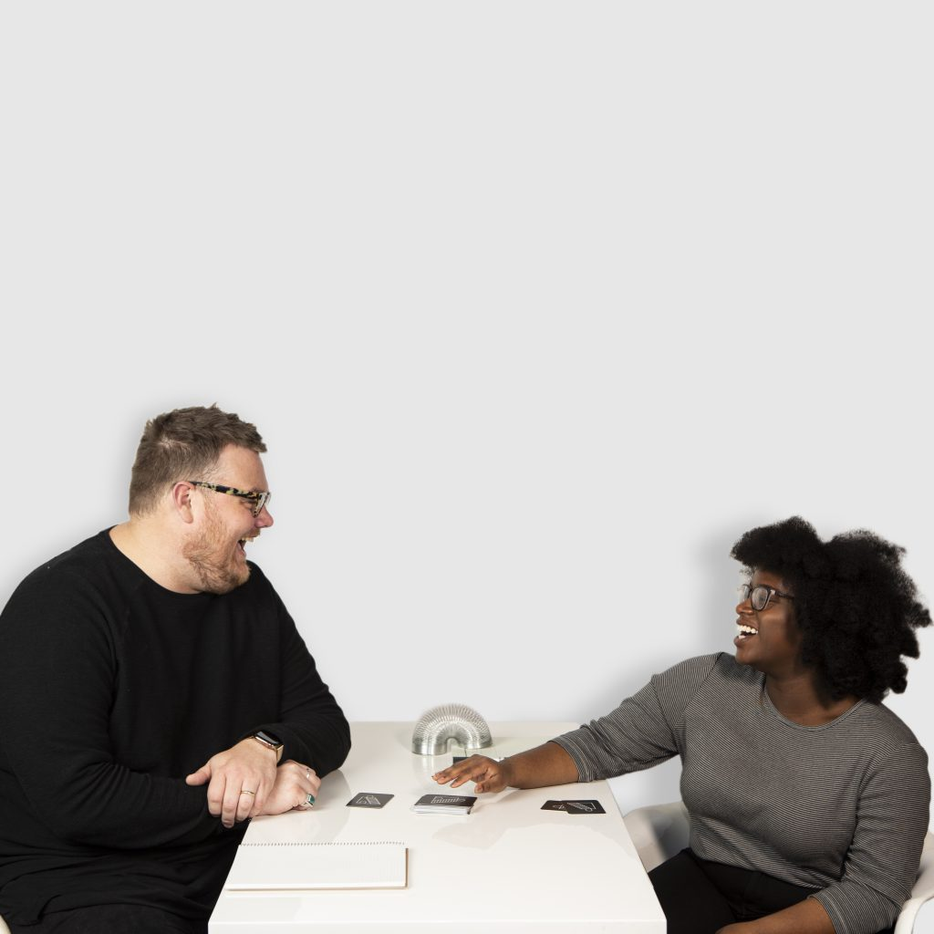 Two individuals laughing across the table from one another