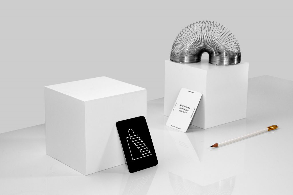 white table with question cards, pencil, and slinky